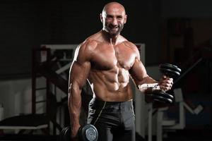 frisk man som tränar biceps i en hälsoklubb foto
