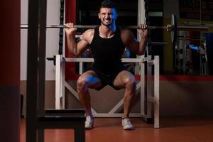 fysiskt passande män som tränar genom att göra knäböj foto