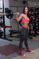 fitness kvinna lyft vikt i gymmet foto