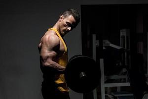 ung man gör övning med tung vikt för biceps