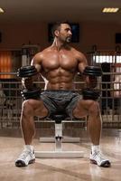 kroppsbyggare som gör tungvikt på axlarna