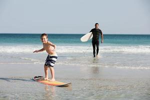 ung pojke som surfar i grunt vatten foto