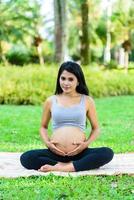 vacker gravid kvinna yoga i parken foto