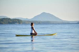 kvinna på stå upp paddleboard, yoga foto