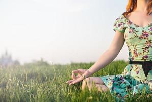 vacker kvinna mediterar i parken foto