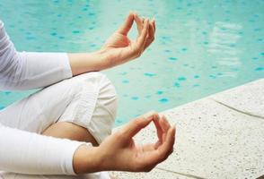 kvinna träning yoga och meditation vid poolen foto
