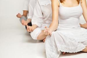 grupp människor som kopplar av och gör yoga i vitt foto