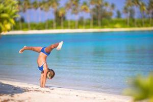 bedårande liten flicka som har kul att göra vagnhjul på tropisk strand foto