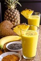 ananas-, banan-, kokos-, gurkmeja- och chiafrönsmoothies foto