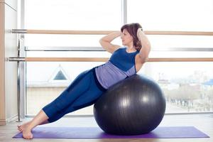 ung flicka som tränar på gymmet med en boll foto