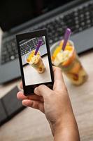 avbildar fruktlunchlåda på kontoret med hjälp av smart telefon foto