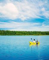 två män paddlar en kajak vid sjön. livsstilskoncept. foto