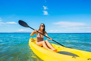 kvinna kajakpaddling i havet på semester foto