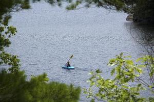 ung kvinna i kajak, vatten i sunapee, new hampshire, horizonta foto