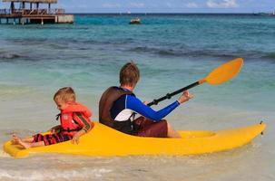 far och son som paddlar kajak på det tropiska havet foto