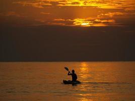 silhuett av man som kajakpaddlar vid solnedgången foto