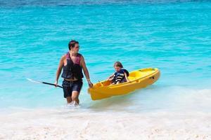 far och son med en kajak på den tropiska stranden foto