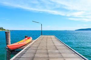 kajak på träpir med blått hav och himmel foto