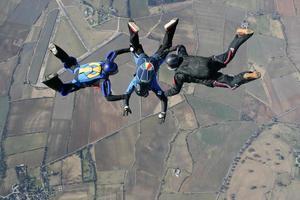 tre fallskärmshoppare i fritt fall foto
