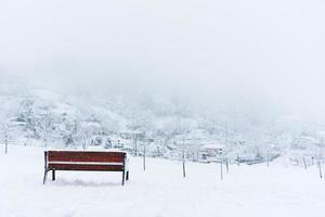 bänk och snöig vinterlandskap foto