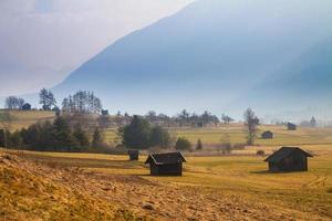 lantligt bergslandskap med en koja foto