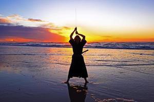 unga samuraikvinnor med japanskt svärd (katana) vid solnedgången på foto