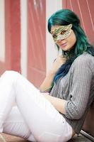 porträtt av ung vacker kvinna med en mask utomhus foto
