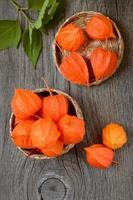 orange vinterkörsbär i korg foto