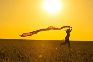 ung kvinna kör på en landsväg vid solnedgången i foto