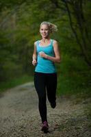 vacker ung kvinna kör i skogen - aktiv löpare spring