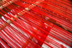 vävvävstol med röd tråd foto