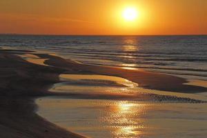 krusningar på stranden vid solnedgången