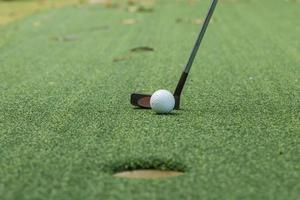 golfboll och tee på grön bana foto