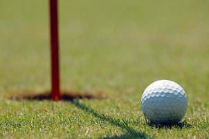 golfspelare på den sätta gröna slå bollen foto