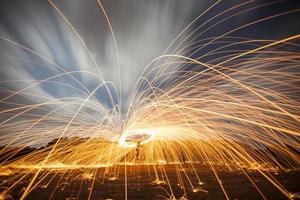 duschar med heta glödande gnistor från snurrande stålull. foto