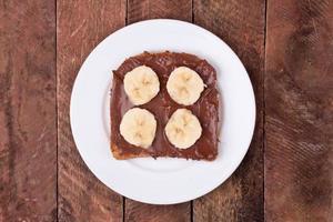 bröd med chokladspridning och banan foto