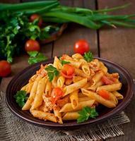 penne pasta i tomatsås med kyckling, tomater foto