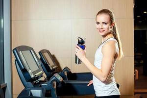 söt flicka som tränar i ett löpband på gymmet foto