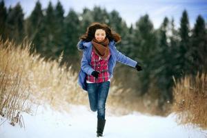 brunett tjej springer i en snöig skog foto