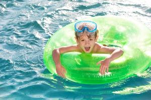 glad liten pojke som simmar i innerröret foto