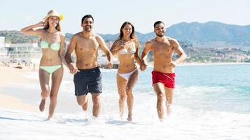 glada människor springer på stranden foto