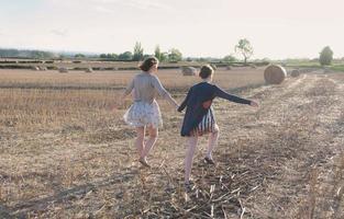 tjejer springer i hö fält