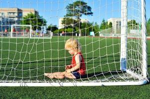 liten flicka baby blond spelar fotboll foto