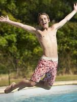 tonårspojke hoppar in i poolen foto