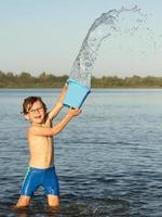 liten pojke som kastar vatten från hinken vid floden foto