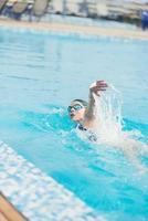 kvinna i skyddsglasögon som simmar främre krypningsstil foto