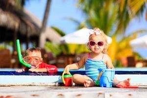 liten pojke och flicka som leker i poolen på stranden foto