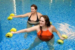 två feta kvinnor i vatten på träning