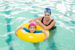 söt liten pojke som lär sig att simma med tränaren foto