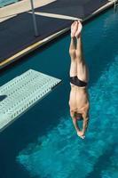 ung man dyker in i poolen foto